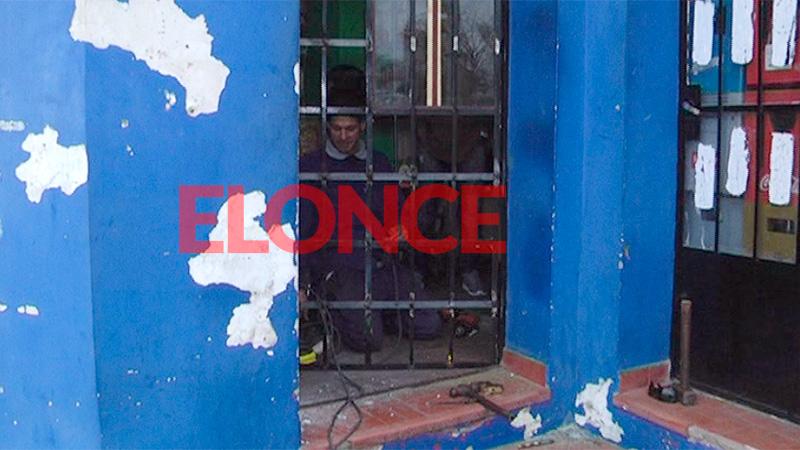 Un herrero repara la reja forzada por los delincuentes en el robo.