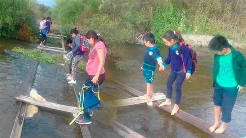 Los chicos cruzan el río como pueden para llegar a la escuela.